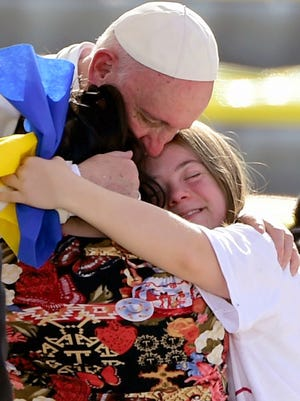 Pope Francis is welcomed by two young faithful during his arrival at the Morelos stadium in Morelia, Michoacan State, Mexico on February 16, 2016.