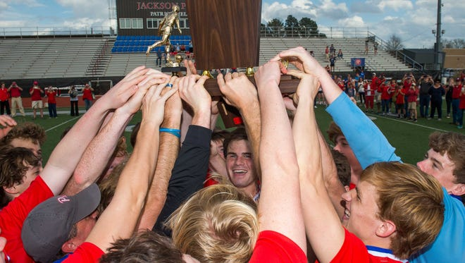 Jackson Prep players hoist the trophy following their win against Jackson Academy in the MAIS Boys Soccer Championship held in Flowood, MS .