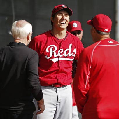 Homer Bailey (center) shares a laugh with manager Bryan Price (right) and general manager Walt Jocketty (left) following a bullpen session.