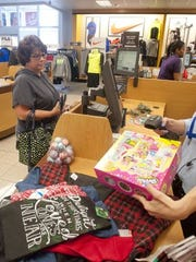 Cheryl Collard of Jeffersontown, in the Kohl's Oxmoor store to buy holiday presents, gets checked out by store associate Jessica Durham, right.