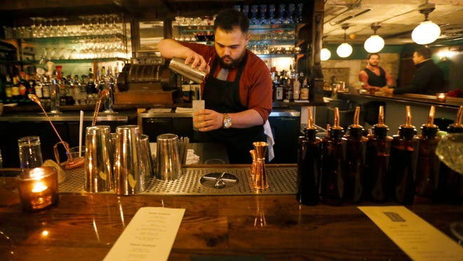Bartender Jay Ryan pours a drink at The Hepburn, a new speakeasy at Dapper Barber in downtown Springfield.