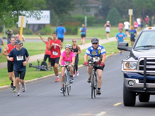 News-Herald Media reporter Marisa Cuellar, wearing bib number 239, rides her bicycle Saturday during the bicycle portion of the Hub City Duathlon in Marshfield.