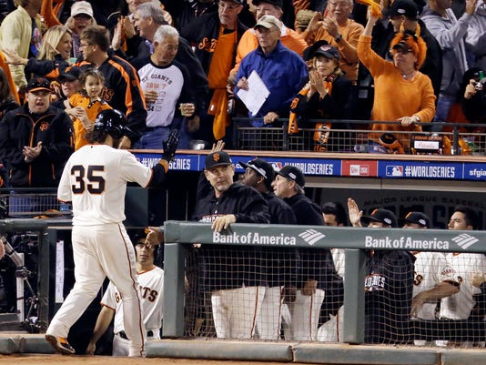 San Francisco Giants' Brandon Crawford heads for the dugout after scoring on an RBI double by Giants' Michael Morse during the sixth inning of Game 3 of baseball's World Series against the Kansas City Royals on Friday, Oct. 24, 2014, in San Francisco. (AP Photo/Charlie Riedel)
