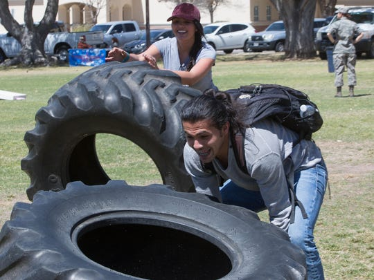 Chantal Orozco, left, a civil engineering student, and Hamad Shaghrood, right, an industrial engineering student, flip truck tires during the New Mexico State University Air Force ROTC's A&M Day. Thursday March 29, 2018.