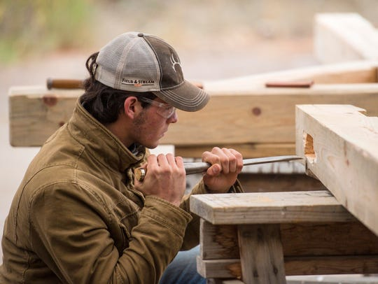 Dylan Roberge of Colchester uses a chisel to shape