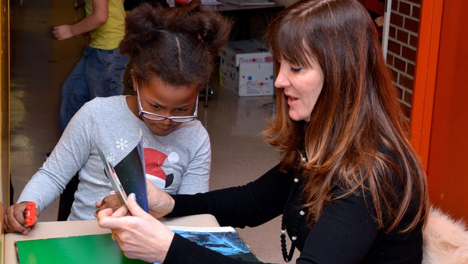 Hurst reads to Mackenzie Giroad-Shorpe and helps her with her work. Though she has a medical practice in Englewood, Hurst spends an hour each week as a Bergen Reads volunteer in the first-grade classroom of teacher Katy Dalie.