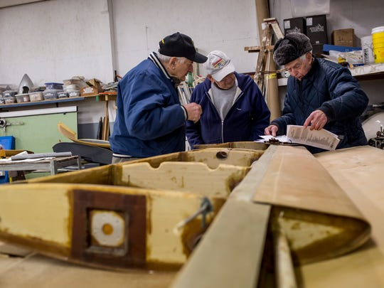 Rich Miskaitis, John Beattie, and Ivan Smith look over paperwork while working on attaching a wing to a fuselage Thursday, Jan. 19, 2017 at the Experimental Aircraft Association Blue Water Chapter 979 at the St. Clair County Airport in Kimball Township.
