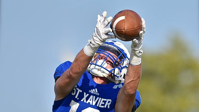 St. Xavier's Jared Kreimer gets his fingertips to a ball from Chase Wolf for a 26-yard touchdown reception Saturday, August 26 at Princeton High School in a win over Hinsdale Central.
