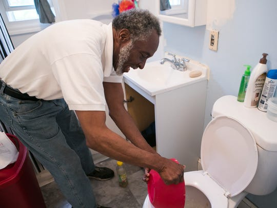 Willis Phelps, Jr. demonstrates how his backed-up pipes require him to empty a bowl from under his sink when it fills with water. His plumbing issues were supposed to be fixed by community volunteers, he said, but they never finished the job.