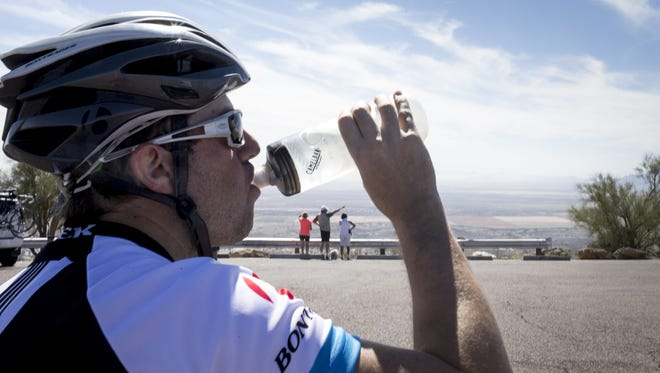 Brian Abraham of Goodyear hydrates after riding his bike, Feb. 29, 2016, to the top of South Mountain Park in Phoenix.