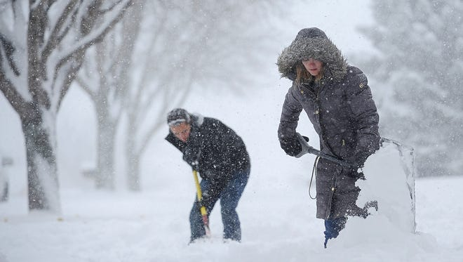 Hope Peterson, 22, and Alex Cutler, 24, both of Sioux Falls, shovel the sidewalk in front of Cutler's parents' house during the first snow of the season Friday, Nov. 20, 2015, in Sioux Falls.