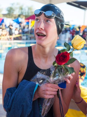Chaparral's Taylor Ruck collects another rose after helping her team win the 200 Yard Free Relay during the State Tournament at the Skyline Aquatic Center in Mesa, AZ on Saturday, Nov. 8, 2014.