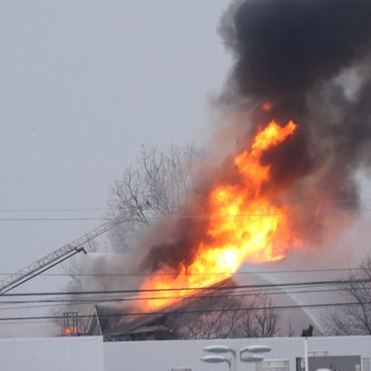 Firefighters work to control a three-alarm fire in