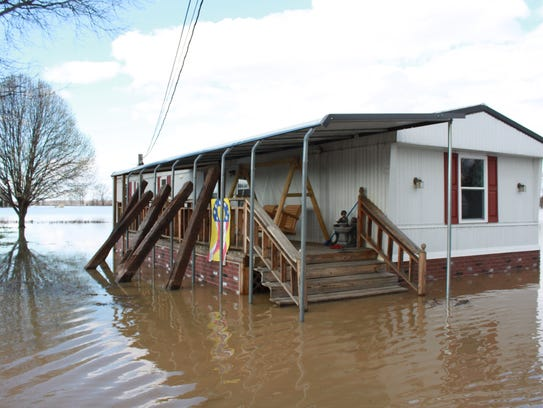 Kim Coble's home in Kenton is surrounded by floodwaters