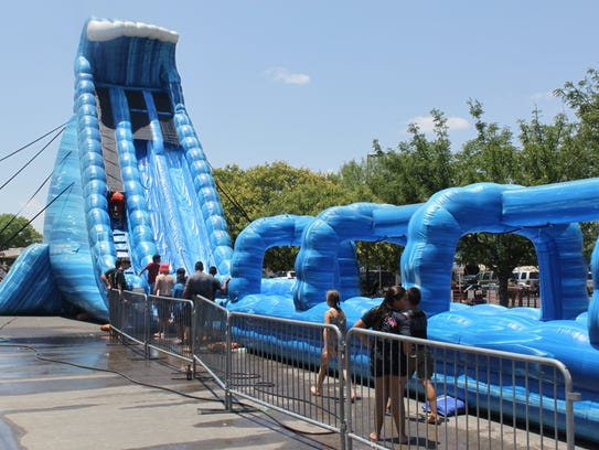 Children play on a giant water slide at the Roswell