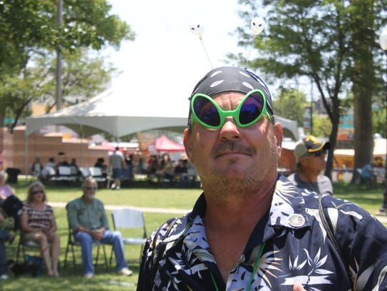 Patrons visit with outdoor vendors sporting Alien-theme