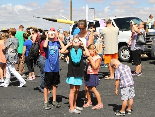 Children look at the solar eclipse Monday at the New