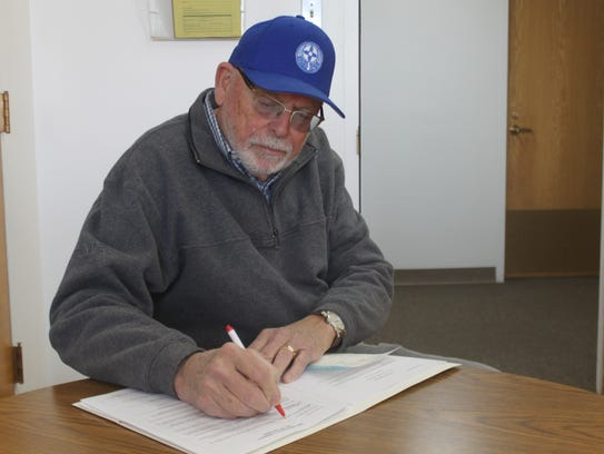 Dick Doss fills out the remaining paperwork so he can