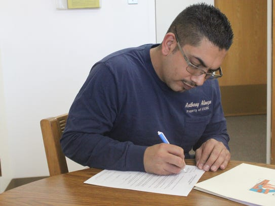 Anthony Alonzo finishes up his paperwork to register