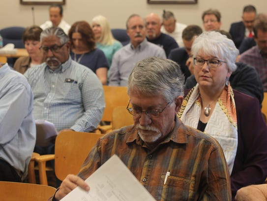 Local officials and residents attend a meeting of the