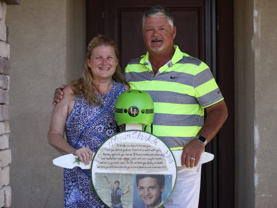 Ginger and Shaun Clark standing with a memorial for