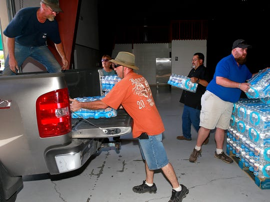 Mike Melott, left, Jason Martinez, center, and Robert McGimsey, right, load up water for their neighbors in Crouch Mesa on Monday at McGee Park. In back is Mike Mestas with the San Juan County Office of Emergency Management.