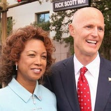 """Lt. Gov. Jennifer Carroll and Gov. Rick Scott stand near the intersection of """"Jennifer Carroll St."""" and """"Rick Scott Way"""" during the inaugural parade Tuesday, Jan. 4, 2011 along Monroe St. in Tallahassee, Florida."""