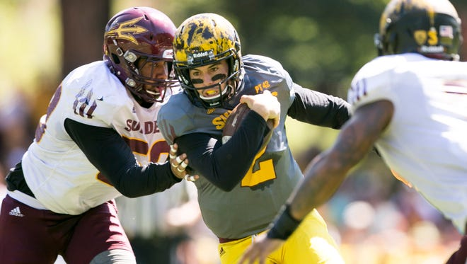 Arizona State quarterback Mike Bercovici carries the ball between ASU defenders Salamo Fiso (left) and D.J. Calhoun during a scrimmage at Camp Tontozona outside of Payson on Aug. 15, 2015.