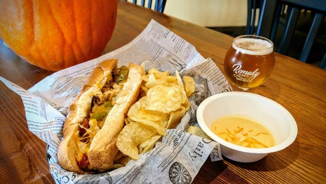 Remedy's expanded menu includes the Chicken Philly Dipper, show here paired with the brewpub's Queen Bee Imperial Honey Cream Ale.