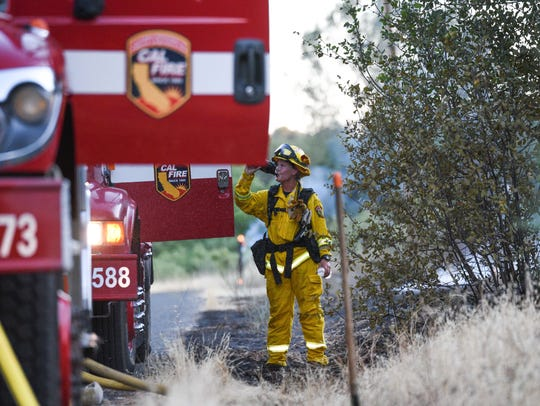 A firefighter takes a water break Saturday at the fire