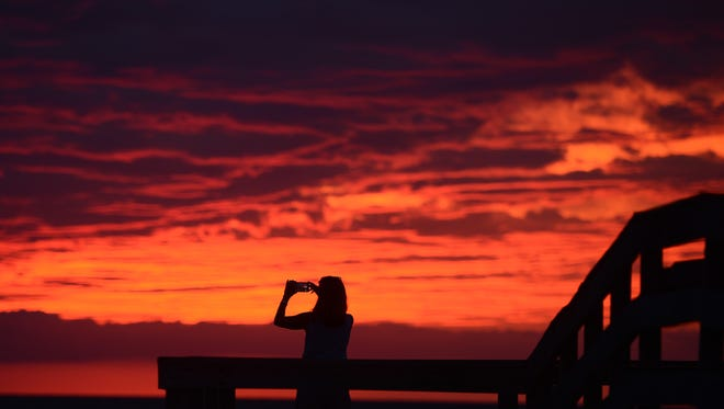Karen Duer-Potts uses her cellphone to take a photograph of the sunset as the outer band of Hermine, which has weakened to a tropical storm, creeps over the beach at Cape Charles, Va., on Sept. 2, 2016.