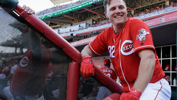 Jay Bruce stands in the Reds' dugout alongside manager