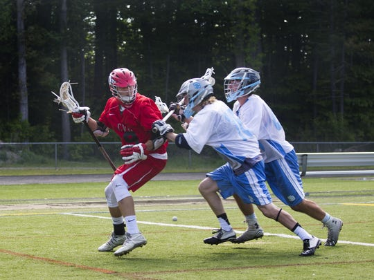 CVU attackman Charlie Bernicke fights to get away from two South Burlington defenders during a high school boys lacrosse game last season.