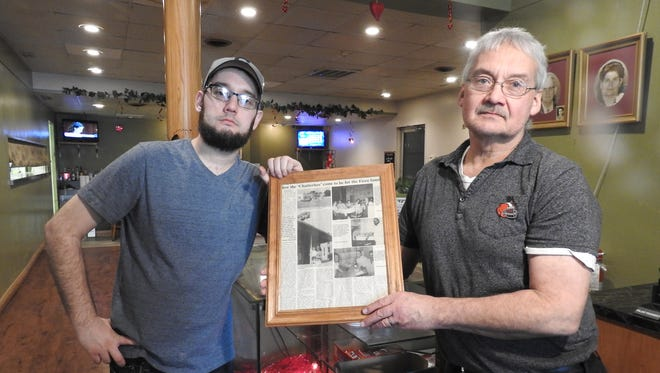 Tim Fiore, owner, and his son, Alex, display articles about Fiore's Restaurant, which is celebrating its 80th year in New Lexington.