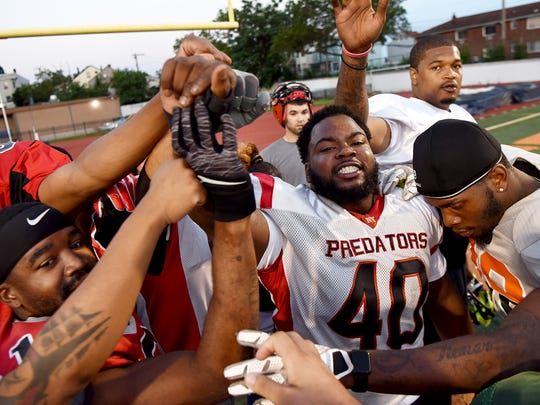 Steven Knight, #40, of Paterson leads his teammates in a pre-practice cheer at Baurle Field on Wednesday, July 5, 2017. Members of the Silk City Sharks, a minor league football team, will have their home opener on Saturday night at 7pm against the Harlem Gators at Baurle Field.
