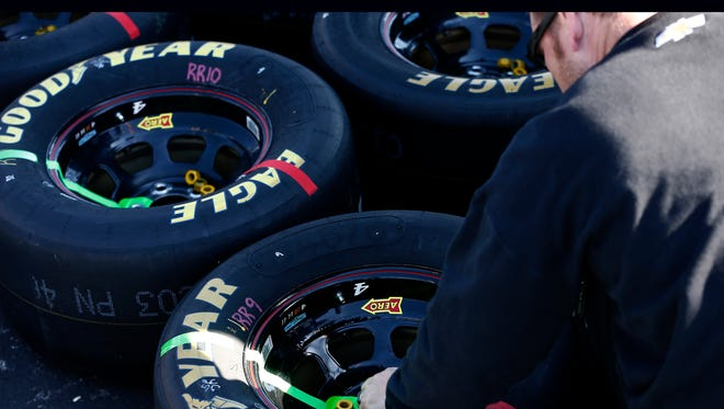 A crew member of Tony Stewart, driver of the #14 Mobil 1 Advanced Fuel Economy Chevrolet, glues lugnuts to rims for use before the NASCAR Sprint Cup Series TOYOTA OWNERS 400 at Richmond International Raceway on April 24, 2016 in Richmond, Virginia.