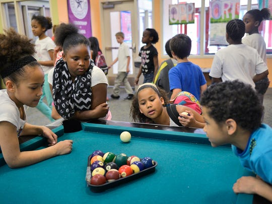 From left: Jada McLean, Enaijah Thomas, Elizabeth Robinson and Donte McLean get ready for a game on the pool table at the Roosevelt Boys & Girls Club in St. Cloud. The children play inside more since fire last year at the adjacent Roosevelt school caused part of their playground to be fenced off.