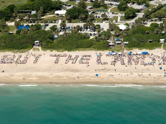 """Attendees of the Citizens for Clean Water rally and beach clean-up spell out """"Buy The Land"""" Saturday, July 2, 2016, at Stuart Beach on Hutchinson Island."""