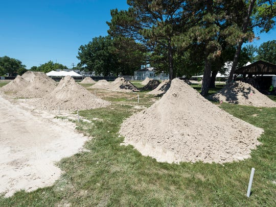 Piles of sand line the grass Tuesday, July 3, 2018