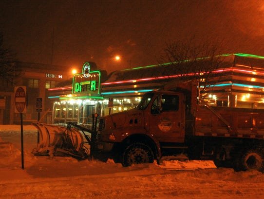 A village snow plow is parked in front of a diner ready