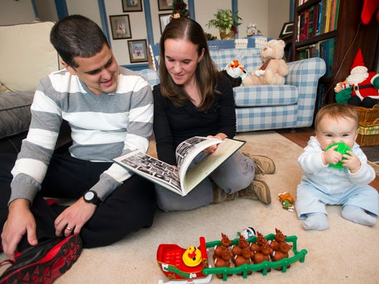 Dustin and Rebecca Rhodes with their 9-month-old son, Michael, look over a 2002 York Catholic High School yearbook Sunday in York Township. The couple met at York Catholic and ran cross country together. Rhodes, a 2002 York Catholic graduate and cross-country runner, will undergo brain surgery Wednesday for an aggressive brain cancer. (YORK DAILY RECORD/SUNDAY NEWS -- PAUL KUEHNEL)