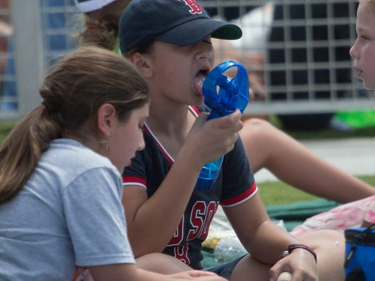 Sophia Bella Carrasquillo of Naples cools off while attending the Boston Red Sox spring training game Tuesday.