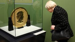 A visitor of the Bode Museum observes  gold coin 'Big