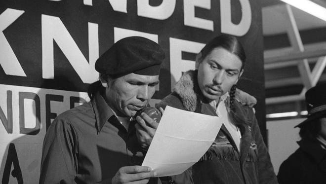 In this March 18, 1973, file photo taken in Wounded Knee, S.D., American Indian Movement leader Dennis Banks, left, reads an offer by U.S. government seeking to effect an end to the Native American takeover of Wounded Knee. Looking on is AIM leader Carter Camp. The family of Banks said he died Sunday, Oct. 29, 2017, at the age of 80.