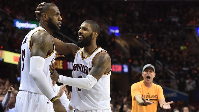 Cleveland Cavaliers forward LeBron James (23) is greeted by guard Kyrie Irving (2) as a fan reacts during the third quarter against the Golden State Warriors in game three of the 2017 NBA Finals at Quicken Loans Arena.