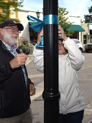 Rick and Cathie Bays team up on Sept. 1 to tie teal ribbons around downtown Northville to bring attention to ovarian cancer. The group was part of the Michigan Ovarian Cancer Alliance's outreach effort on that day.