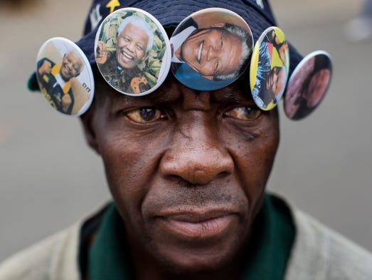Mac Arthur Mti wears badges for sale with the image of Nelson Mandela in Soweto, Johannesburg.