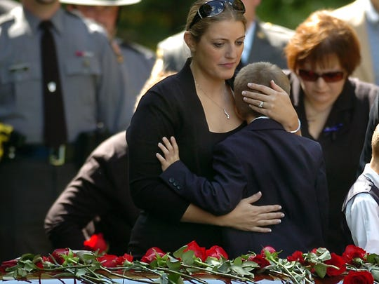 Tiffany Dickson embraces her 7-year-old son Bryon III, in front of the casket of her husband Pennsylvania State Trooper Cpl. Bryon Dickson on Thursday, Sept. 18, 2014 at the Dunmore Cemetery in Dunmore, Pa.  Dickson was killed on Friday night in an ambush shooting at the state police barracks in Blooming Grove Township. Authorities are looking for 31-year-old Eric Frein, of Canadensis, who has been charged with killing one trooper and wounding another outside the barracks.