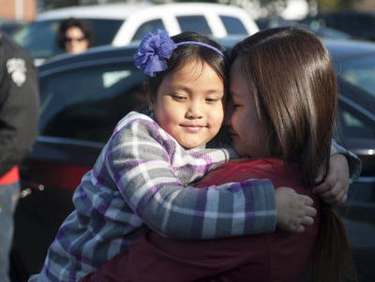 Jessica Frantes, left, hugs her sister Maria as Winslow