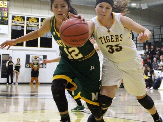 Daniella Martinez, right, battles Mikayla Sago for possession Tuesday night. Mayfield defeated Alamogordo 58-29.